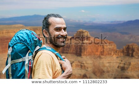 close up of man with backpack over grand canyon Stock photo © dolgachov