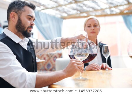 Young bearded male sommelier or bartender pouring red cabernet into wineglass Stock photo © pressmaster