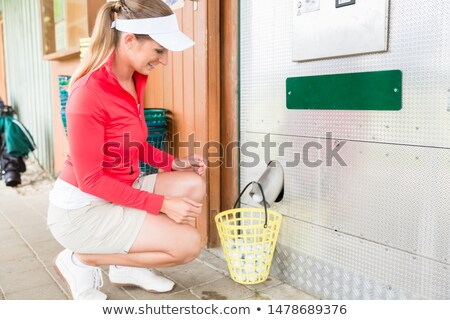 Female golf player filling the basket with golf ball Stock photo © Kzenon