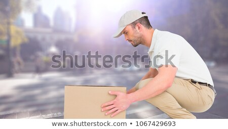 Delivery man picking up box against blurry street with flare Stock photo © wavebreak_media