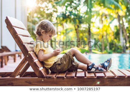 A cute little boy is using a smartphone lying on a deckchair by the pool. primary education, friends Stock photo © galitskaya