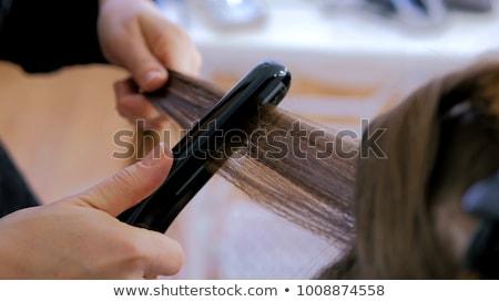 Hairdresser using flat iron on hair of woman customer Stock photo © Kzenon