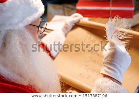 Gloved Santa Claus with feather in hand looking through nice list Stock photo © pressmaster