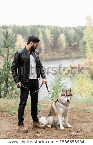 Guy in casualwear holding leash of his purebred pet during chill Stock photo © pressmaster