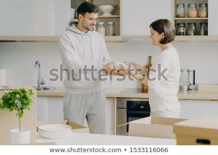 Horizontal shot of smiling couple unpack cardboard boxes in new kitchen, man passes plates to woman, Stock photo © vkstudio