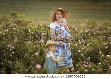Young beautiful mother with a child stands in an agricultural field with a flowering rose Stock photo © ElenaBatkova