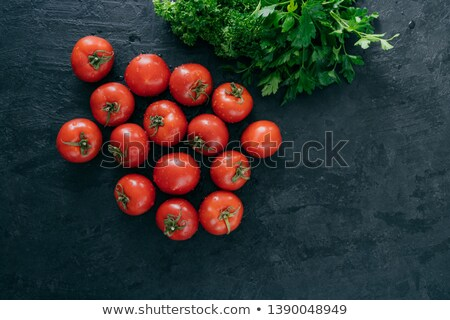 Top view of fresh red heirloom tomatoes and green parsley on black background. Vegetables containig  Stock photo © vkstudio