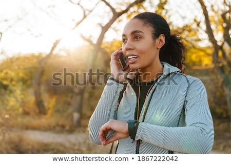 Image of african american sportswoman using cellphone and smartwatch Stock photo © deandrobot