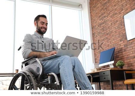 Young man in a wheelchair using a laptop computer in the workplace Stock photo © photography33