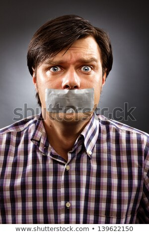 Angry young man with duct tape on his mouth Stock photo © stockyimages