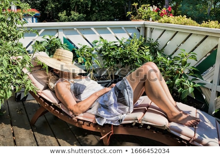 Stock photo: Woman sunbathing on a wooden deck