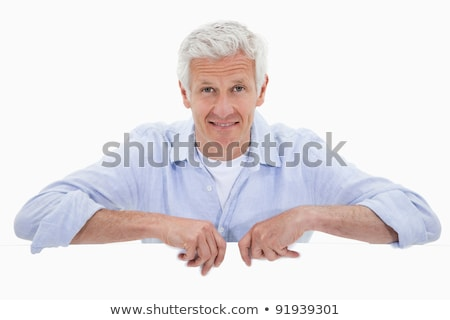 Portrait of a smiling mature man standing behind blank panel against a white background Stock photo © wavebreak_media