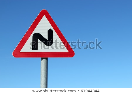 Stock photo: British double bend road sign and blue sky.