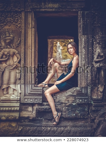 beautiful asian woman with stone wall stock photo © witthaya