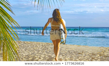 fit surfer girl running to the sea with her surfboard stock photo © wavebreak_media