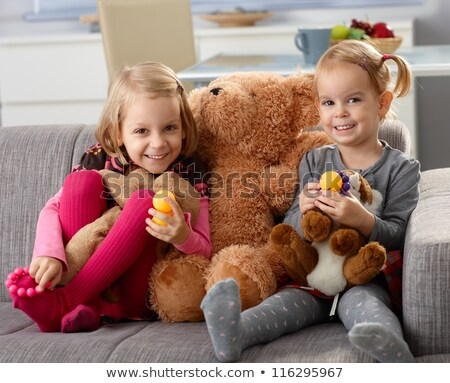 Little girl with big teddy bear sitting on sofa in the living room stock photo © id7100
