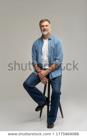 Attractive fashion man sitting on a chair  Stock photo © feedough