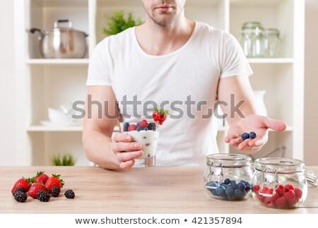 Közelkép férfi finom joghurt friss bogyók Stock fotó © tommyandone