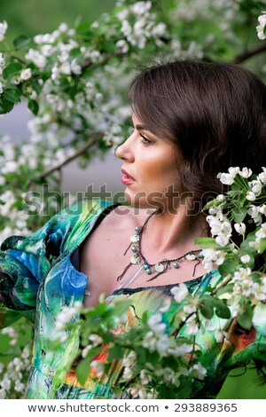 beautiful girl standing at blossoming tree in the garden stock photo © artfotodima
