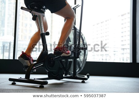 View from below of Muscular man using spinning bicycle Stock photo © deandrobot
