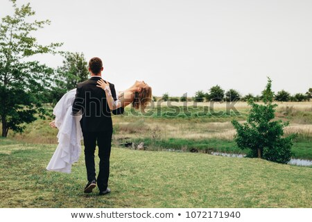 groom carries bride in his arms stock photo © tekso