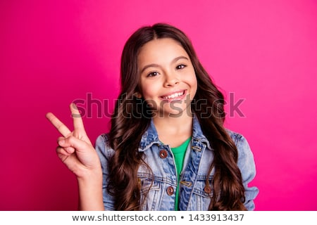 Young girl holding two fingers up in a peace sign Stock photo © deandrobot