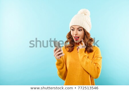 Woman dressed in warm sweater talking by phone. Stock photo © deandrobot