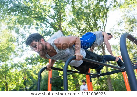 Strong young man supporting his friend while doing pull-ups Stock photo © Kzenon
