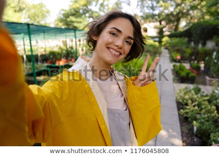 Stock photo: Cute woman gardener standing over flowers plants in greenhouse make selfie by camera.