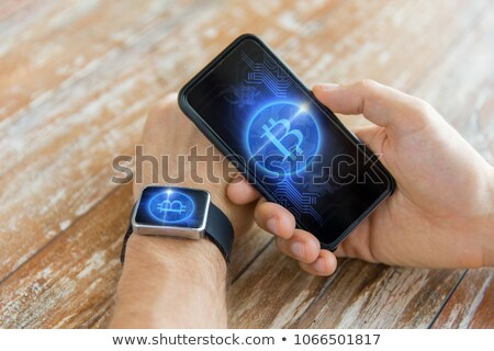 close up of hands with bitcoin on smart watch stock photo © dolgachov