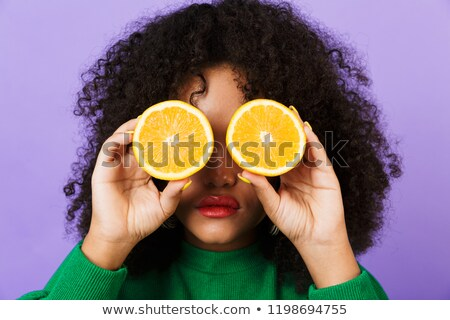 Serious pretty african woman isolated over violet background holding orange covering eyes. Stock photo © deandrobot