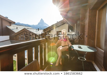 silhouette of woman in sunshine at window with view on sunset in mountains stock photo © ruslanshramko