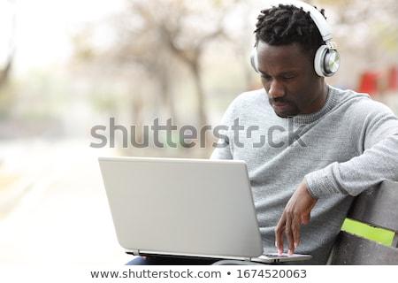 jonge · man · luisteren · naar · muziek · laptop · computer · boek · telefoon - stockfoto © deandrobot