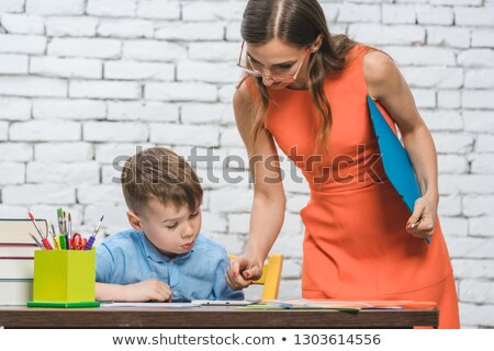 Student boy doing work in school supervised by his teacher Stock photo © Kzenon