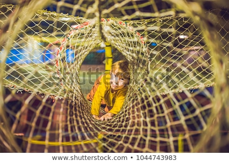 the boy passes the obstacle course in the sports club stock photo © galitskaya