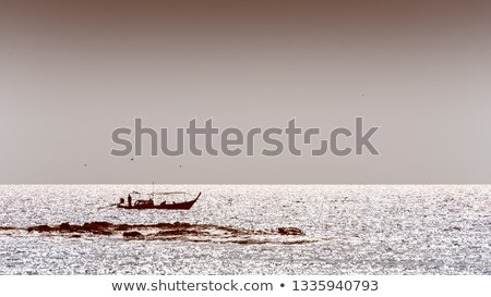 Silhouette native fishing boat in sepia colors Stock photo © Yongkiet