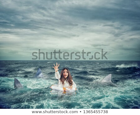 businesswoman with lifebelt surrounded by sharks asks help stock photo © alphaspirit
