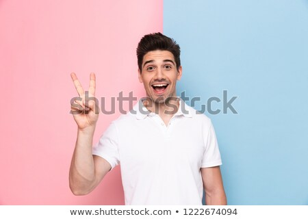 Image of positive man 30s having stubble showing peace sign with Stock photo © deandrobot