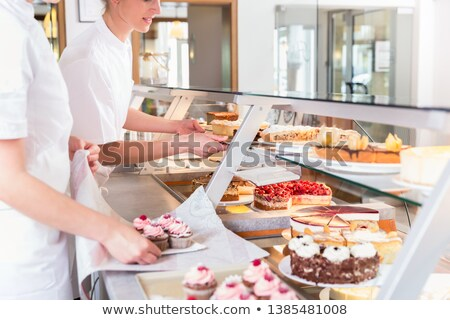 Women in pastry shop filling up sales display with pies Stock photo © Kzenon