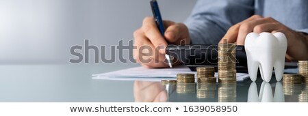 white tooth in front of man calculating bill stock photo © andreypopov