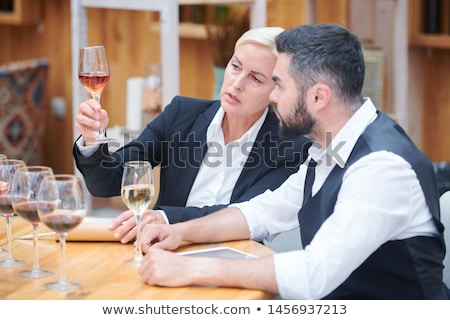 Pretty sommelier with glass of white wine giving its chracteristics Stock photo © pressmaster