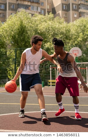 Two intercultural basketball playmates playing or training on the court Stock photo © pressmaster
