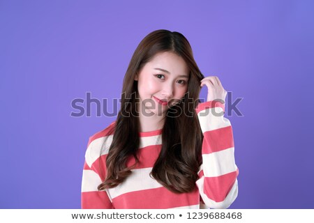 Pretty girl in winter clothes looking up with folded arms. Stock photo © lichtmeister