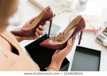Pair of fashionable leather high-heeled shoes held by young female shopper Stock photo © pressmaster