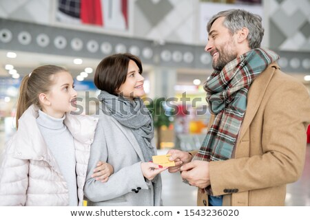 Happy man giving credit card to wife and daughter before shopping in the mall Stock photo © pressmaster