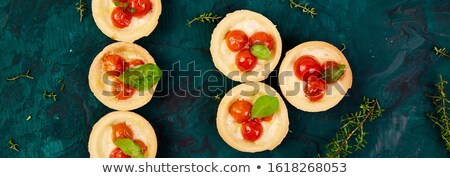Banner with Mini tarts with cherry tomatoes with mozzarella cheese on green background. Stock photo © Illia