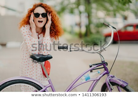 Happy woman has curly foxy hair, leans at saddle of her bicycle, has outdoor promenade during sunny  Stock photo © vkstudio