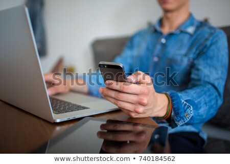 Stock photo: Man reading magazine and sending text message