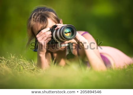 Stock photo: pretty young woman with a DSLR camera outdoors, taking pictures