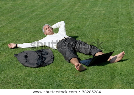 Stock photo: Senior man lying on the grass with a computer